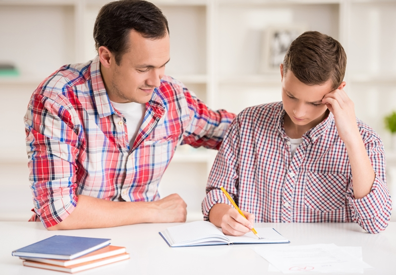 A father helps his son with homework