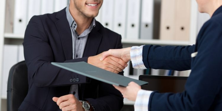 a boss shakes the hand of a new-hire