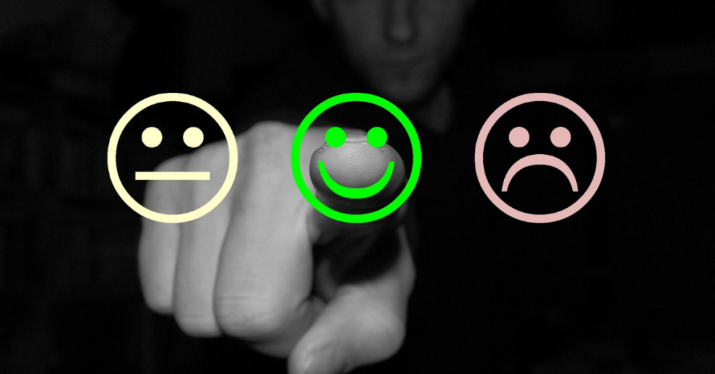 person pointing to a happy face icon that's green nps survey customer service in education