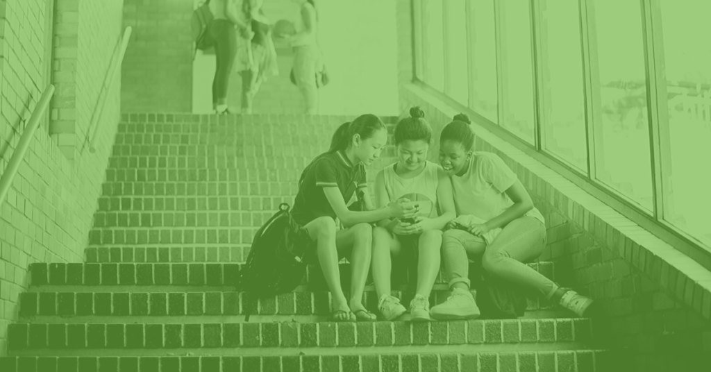 Three teenage girls looking at a smartphone on stairs at school edtech trends 2020